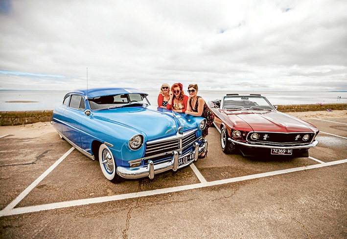 Rock N Rollers Ron Smith, Stephen Wilkinson, Kez Bailey and Julie Nolo with vintage cars on Roesbud beack foreshore.